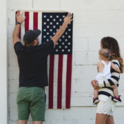 Image of a family hanging up an American flag
